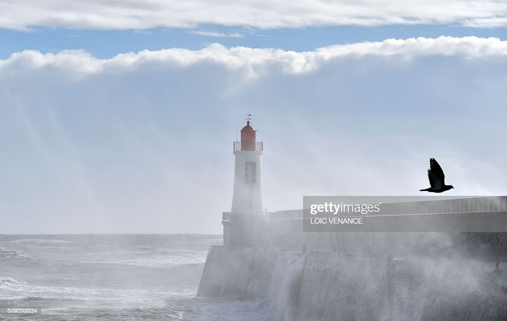 Waves breaks against a pier and the lighthouse in Les Sables-d'Olonne, western France, on February 9, 2016. High winds buffeted northwestern Europe on February 8, leaving one woman in France in a coma after she was hit by an advertising hoarding. Electricity was cut to 5,000 homes in northern France. / AFP / LOIC VENANCE