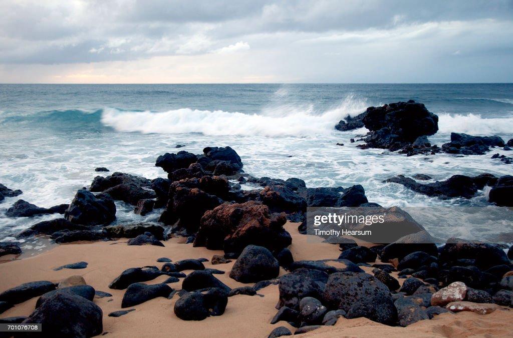 Waves crash against lava rock on a beach : Stock Photo