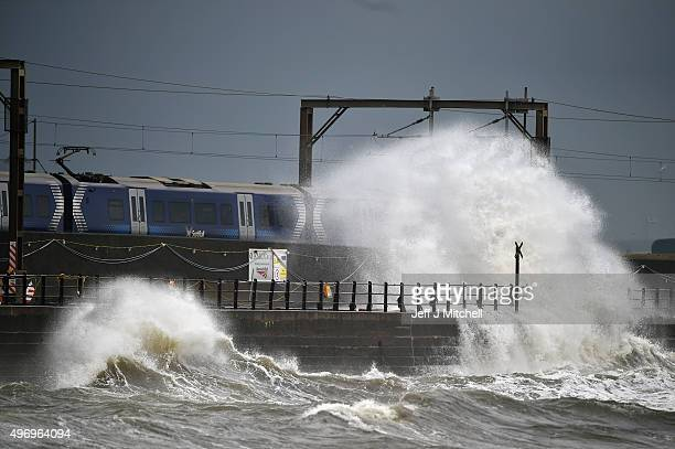 Waves crash against the sea wall as a train passes through on November 13 2015 in Saltcoats Scotland Storm Abigail has closed schools on the Western...