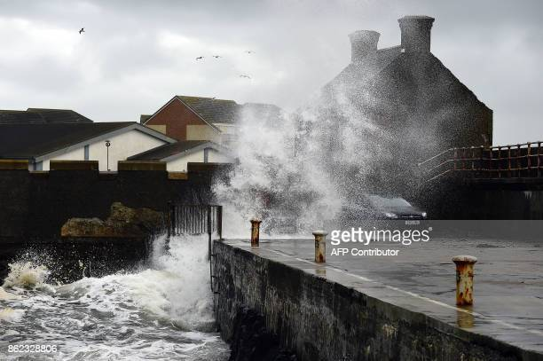 Waves crash as the remnants of Storm Ophelia hit Saltcoats on the west coast of Scotland on October 17 2017 Train services between Glasgow and...
