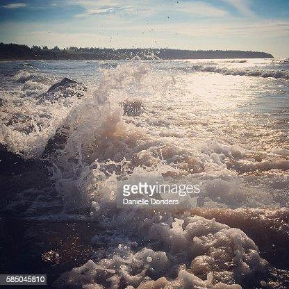 Waves crash on red sandstone rocks on a beach on Prince Edward Island