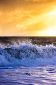 Waves break over the shingle beach at Hengistbury Head, Dorset with the Isle of Purbeck visible in the distance against the sun.