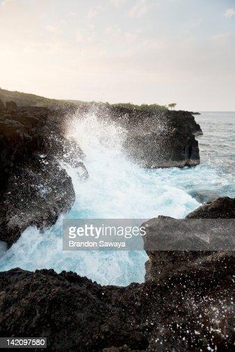 Waves crash over cliffs of lava rock.