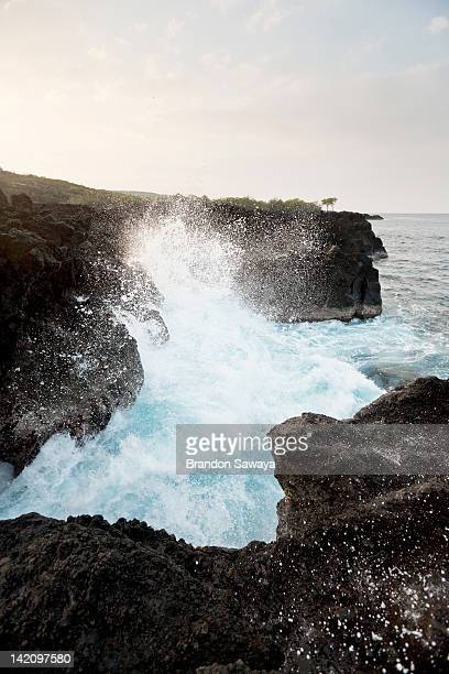 Waves crash over cliffs of lava rock.