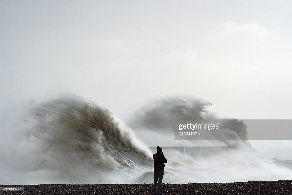 Waves crash over Newhaven harbour on the south coast of England on February 8, 2016, as the latest storm continues across the south of England. Heavy winds buffeted Europe's northwestern flank on Monday, forcing road closures and disrupting rail and ferry services in southern England and prompting high wave alerts in France's Brittany region. Gales and heavy rain with wind speeds of nearly 100 miles per hour (155 kilometres per hour) battered southern England and Wales, with flood warnings issued in more than 50 areas. / AFP / GLYN KIRK