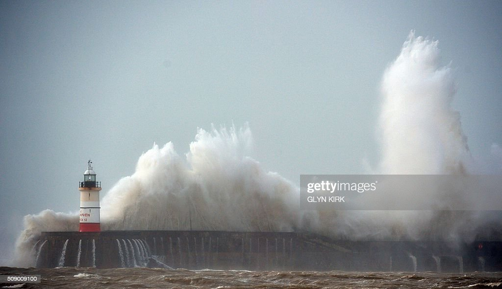 Waves crash over Newhaven Lighthouse on the south coast of England on February 8, 2016, as the latest storm hits the country. Heavy winds buffeted Europe's northwestern flank on Monday, forcing road closures and disrupting rail and ferry services in southern England and prompting high wave alerts in France's Brittany region. Gales and heavy rain with wind speeds of nearly 100 miles per hour (155 kilometres per hour) battered southern England and Wales, with flood warnings issued in more than 50 areas. / AFP / GLYN KIRK
