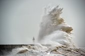 TOPSHOT Waves crash over Newhaven Lighthouse on the south coast of England on February 8 as the latest storm hits the country Heavy winds buffeted...