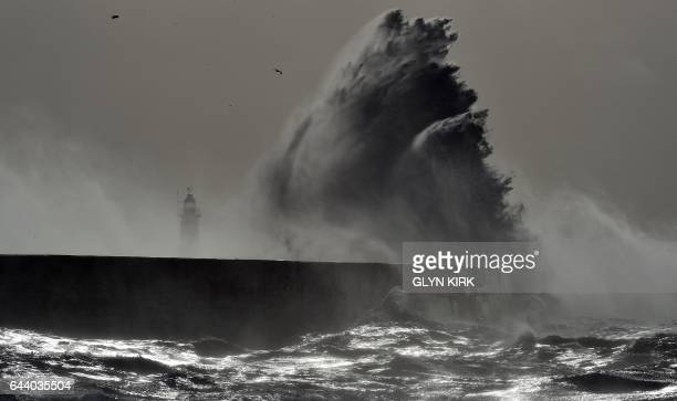 TOPSHOT Waves crash over Newhaven Lighthouse on the south coast of England on February 23 2017 as Storm Doris hits the country / AFP / GLYN KIRK