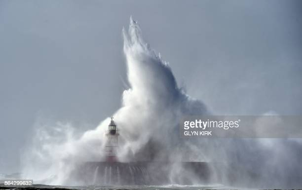 TOPSHOT Waves crash over Newhaven Lighthouse on the south coast of England on October 21 2017 as Storm Brian hits the country / AFP PHOTO / GLYN KIRK