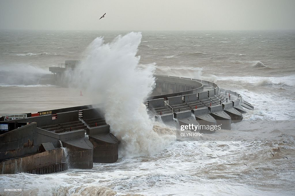 Waves crash over the breaker outsiude Brighton Marina in Brighton, on the south coast of England on February 8, 2016, as the latest storm hits the country. Heavy winds buffeted Europe's northwestern flank on Monday, forcing road closures and disrupting rail and ferry services in southern England and prompting high wave alerts in France's Brittany region. Gales and heavy rain with wind speeds of nearly 100 miles per hour (155 kilometres per hour) battered southern England and Wales, with flood warnings issued in more than 50 areas. / AFP / GLYN KIRK