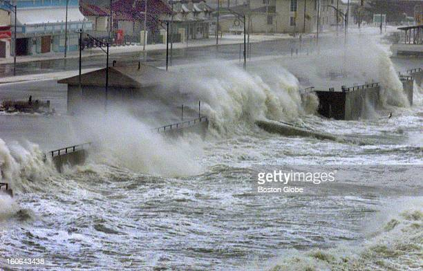 Waves crash over the seawall at Nantasket Beach during early morning high tide