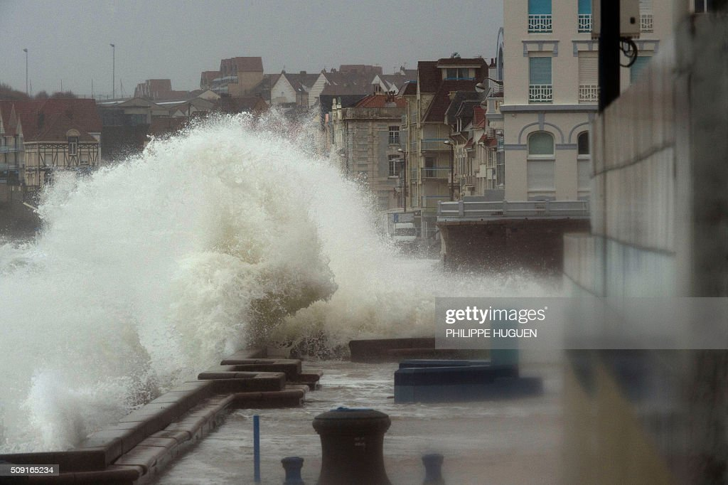 Waves crash over the Wimereux breakwater, northern France, on February 9, 2016. High winds buffeted northwestern Europe on February 8, leaving one woman in France in a coma after she was hit by an advertising hoarding. Electricity was cut to 5,000 homes in northern France. / AFP / PHILIPPE HUGUEN