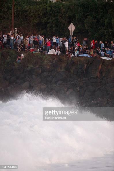 Waves crash up against rocks as a large crowd gathers along Kamehameha Highway at Waimea Bay to watch the 2009 Eddie Aikau BigWave Invitational on...