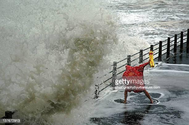 Waves crashing by bridge