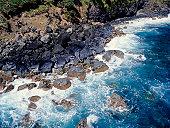 Waves crashing on rocky coastline, aerial view