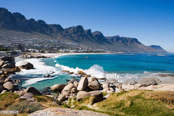 Waves crashing onto Camps Bay beach with Twelve Apostles Mountains in distance.