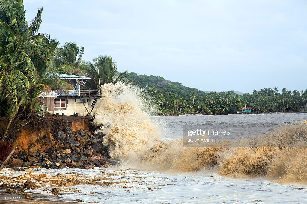 Waves hit a house along the sea near Cayenne on January 15, 2013. The coast of Guyana switched to 'red alert' today as several houses of Rémire-Montjoly (10 km from Cayenne) have been 'damaged' due to high tides, the prefecture of Guyana said in a statement.