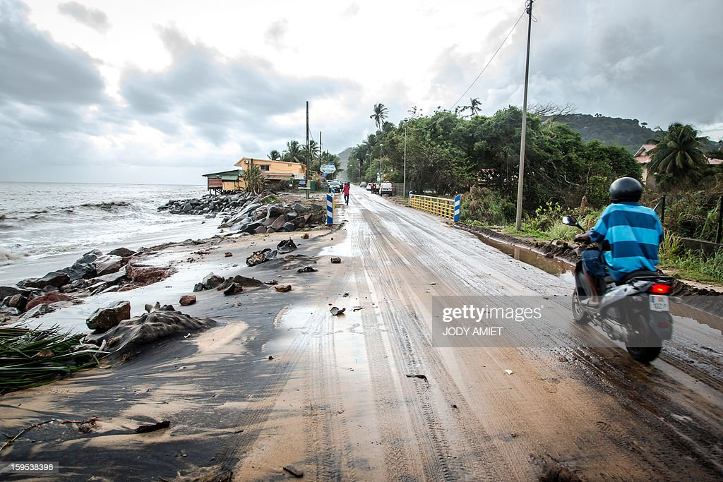 Waves hit the road along the sea near Cayenne on January 15, 2013. The coast of Guyana switched to 'red alert' today as several houses of Rémire-Montjoly (10 km from Cayenne) have been 'damaged' due to high tides, the prefecture of Guyana said in a statement.