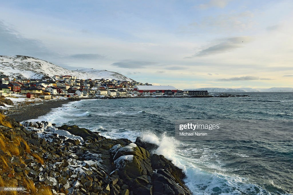 Waves in a rocky bay, buildings of the Honningsvag settlement at the back, Mageroya island, Finnmark County, Norway