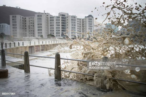 TOPSHOT Waves of foam and seawater crash into Three Anchor Bay in Cape Town on June 7 as an intense storm hits South Africa's west coast The...