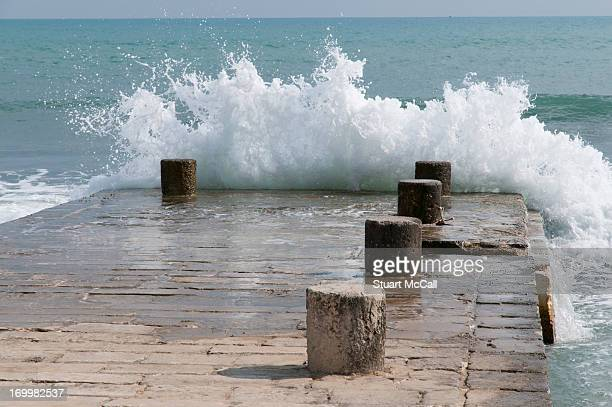 Waves splashing over stone pier