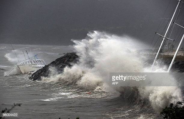 Waves stirred up by Cyclone Ului batter former Sydney to Hobart race yacht 'Anaconda II' and the trawler 'Silvelle' against the seawall at Airlie...