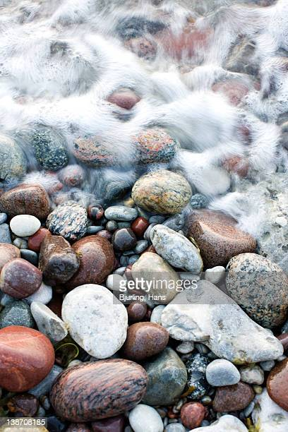 Waves sweeping over pebbles on beach