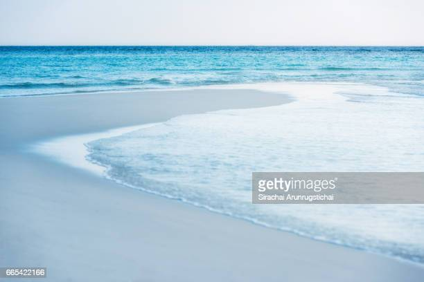 Waves washes over idyllic white sandy beach