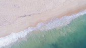 Waves Washing onto the Sandy Beach Viewed From Above Displaying Textures and Colors Diagonally on a Summer Day