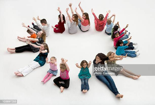 Waving children sitting a circle.