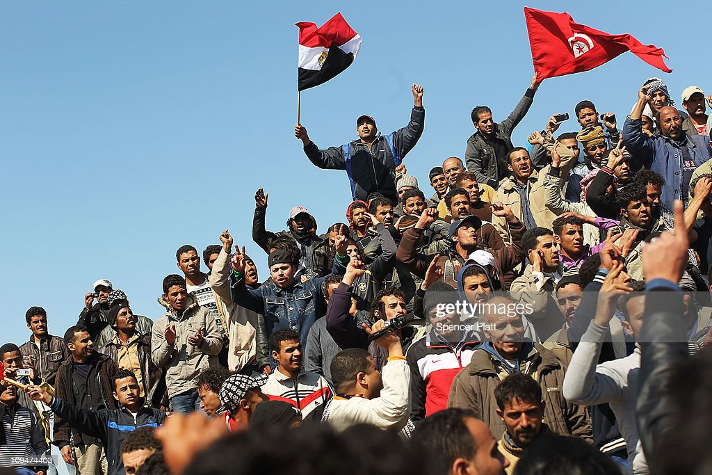 Waving Egyptian and Tunisian flags migrant workers who recently fled into Tunisia from Libya demand to be taken home during a demonstration at a...