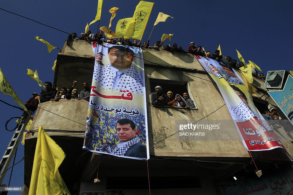 Waving Fatah's yellow flags on the top of a building, supporters of Palestinian president Mahmud Abbas's party hold on January 4, 2013 their first mass rally in Gaza since Hamas seized control of the territory in 2007. Hamas, in a sign of reconciliation with Fatah, permitted the rally to go ahead as the climax of a week of Gaza festivities celebrating the 48th anniversary of Fatah taking up arms against Israel. AFP PHOTO / SAID KHATIB