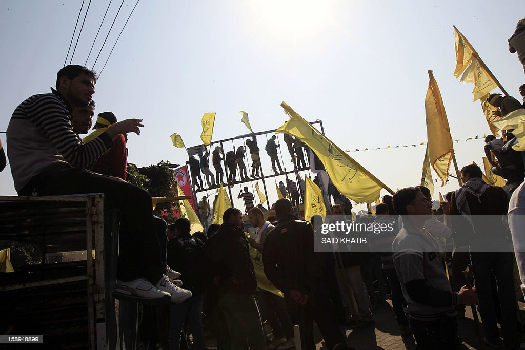 Waving Fatah's yellow flags on the top of a wall, young supporters of Palestinian president Mahmud Abbas's party hold on January 4, 2013 their first mass rally in Gaza since Hamas seized control of the territory in 2007. Hamas, in a sign of reconciliation with Fatah, permitted the rally to go ahead as the climax of a week of Gaza festivities celebrating the 48th anniversary of Fatah taking up arms against Israel. KHATIB