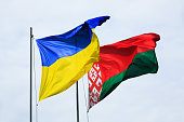 Symbol of friendship and partnership. Waving flags of Ukraine and Belarus on flagpoles against the sky