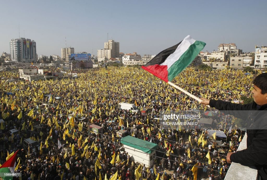 Waving national flags (R) and Fatah's yellow banners, hundreds of thousands of supporters of Palestinian president Mahmud Abbas's party held on January 4, 2013 their first mass rally in Gaza since Hamas seized control of the territory in 2007. Hamas, in a sign of reconciliation with Fatah, permitted the rally to go ahead as the climax of a week of Gaza festivities celebrating the 48th anniversary of Fatah taking up arms against Israel. AFP PHOTO / MOHAMMED ABED