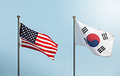 waving the American flag, the Star-Spangled Banner, the Stars and Stripes and south korean flag on blue sky, korean and us alliance, us and korean alliance