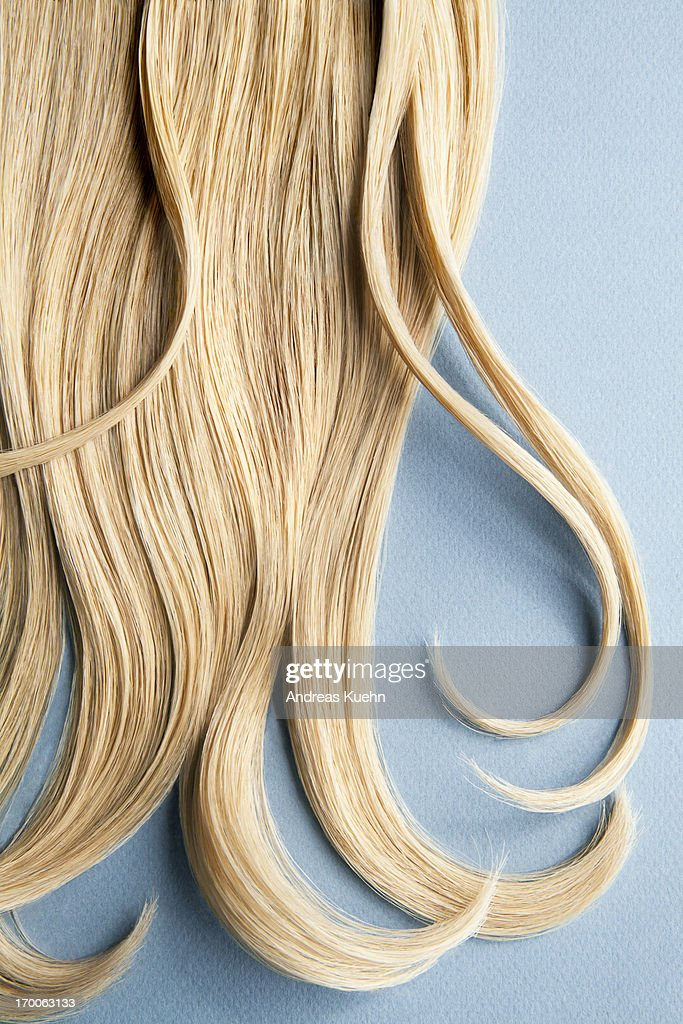Wavy blond hair on blue background.