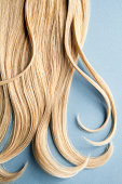 Wavy blond hair on blue background.