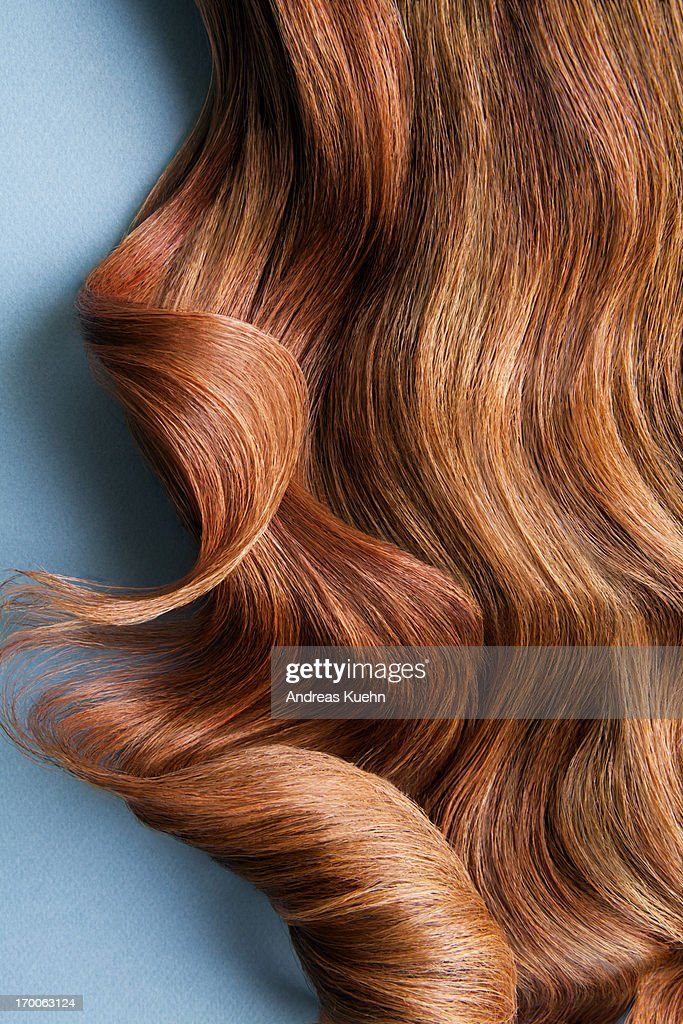 Wavy red hair on a blue background. : Stock Photo