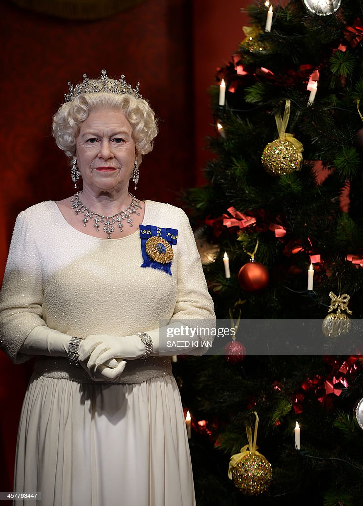 A wax figure of Britain's Queen Elizabeth II next to a Christmas tree at Madame Tussauds Sydney on December 19, 2013. Madame Tussauds Sydney unveiled the Prince William and Princess Catherine wax figures for the first time as husband and wife in a Christmas-theme surrounding with Queen Elizabeth II. AFP PHOTO / Saeed KHAN