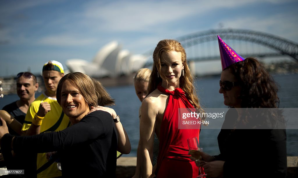 Wax figures of Australian actor Nicole Kidman (C) and singer Keith Urban (L) are displayed during a celebration of the first anniversary of Madame Tussauds Sydney in front of the Harbour Bridge and the Opera House in Sydney on April 17, 2013. Madame Tussauds Sydney organised a birthday party with wax figures of Australian celebrities including Nicole Kidman, Keith Urban, Dannii Minogue, Miranda Kerr, Eric Bana and Lleyton Hewitt. AFP PHOTO / Saeed Khan