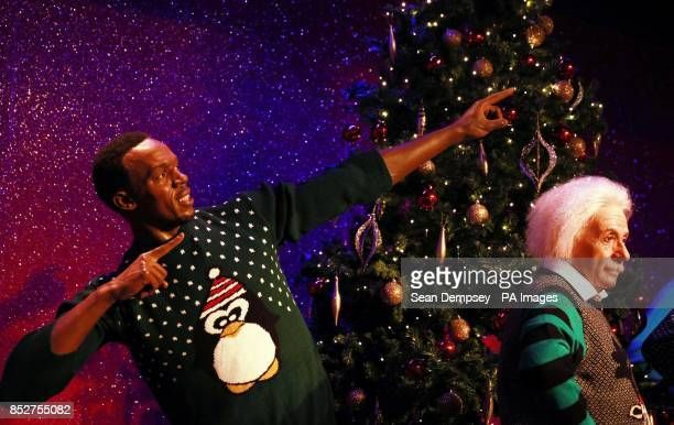 Wax figures of Usain Bolt and Albert Einstein as they don Christmas sweaters to show their support for Save the Childrens Christmas Jumper Day to...