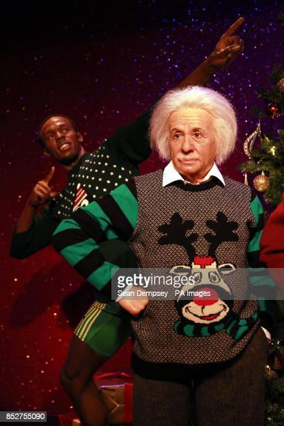 Wax figures of Usain Bolt and Albert Einstein as they don Christmas sweaters to show their support for Save the ChildrenOtildes Christmas Jumper Day...
