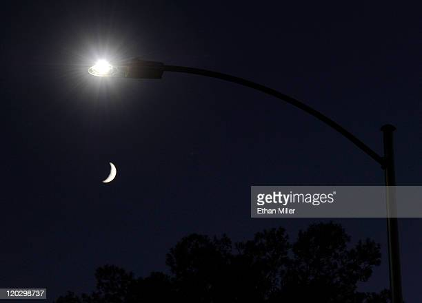 A waxing crescent moon is seen behind a streetlight with a newlyinstalled LED fixture August 3 2011 in Las Vegas Nevada The city is replacing 6600...