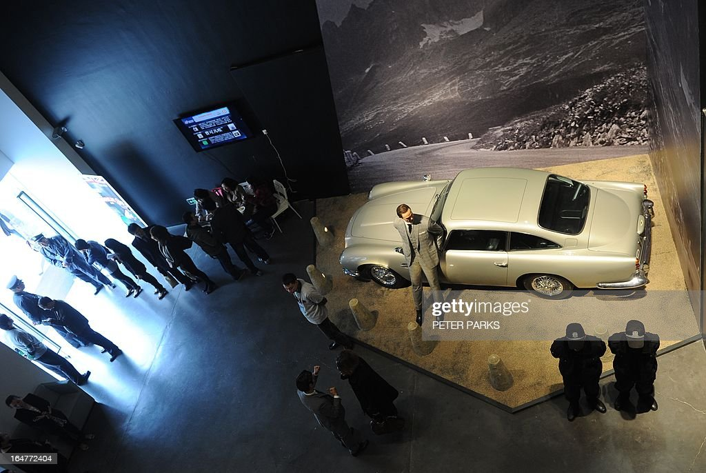 A waxwork of Sean Connery as James Bond (C) stands next to a replica scale model of Bond's Aston Martin DB5 at an exhibition on the fictional British spy in Shanghai on March 28, 2013. The exhibition opened in Shanghai just weeks after the Communist government's censors cut parts of the latest film in the franchise, 'Skyfall' with a scene showing prostitution in Macau, a special administrative region of China, was removed, as was a line in which Bond's nemesis mentions being tortured by Chinese security agents. AFP PHOTO/Peter PARKS
