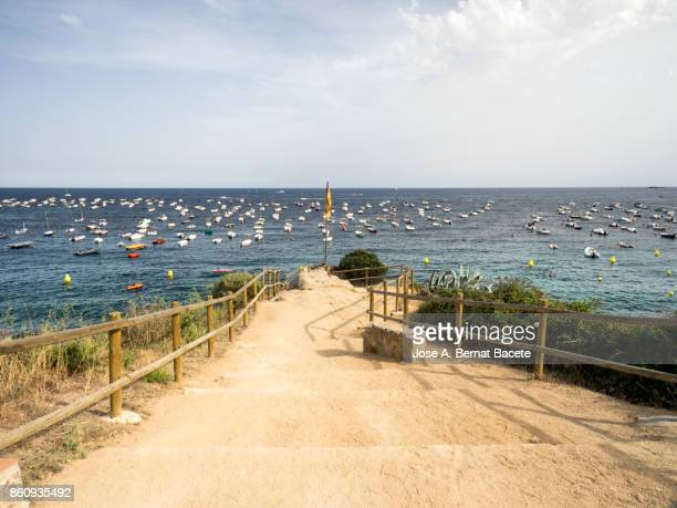 Way that leads to a maritime viewing-point on the coast next to the sea, with anchored pleasure crafts and a great mast with the independence flag of Catalonia. Viewpoint on the Costa Brava in the village of Calella. Catalonia, Spain.