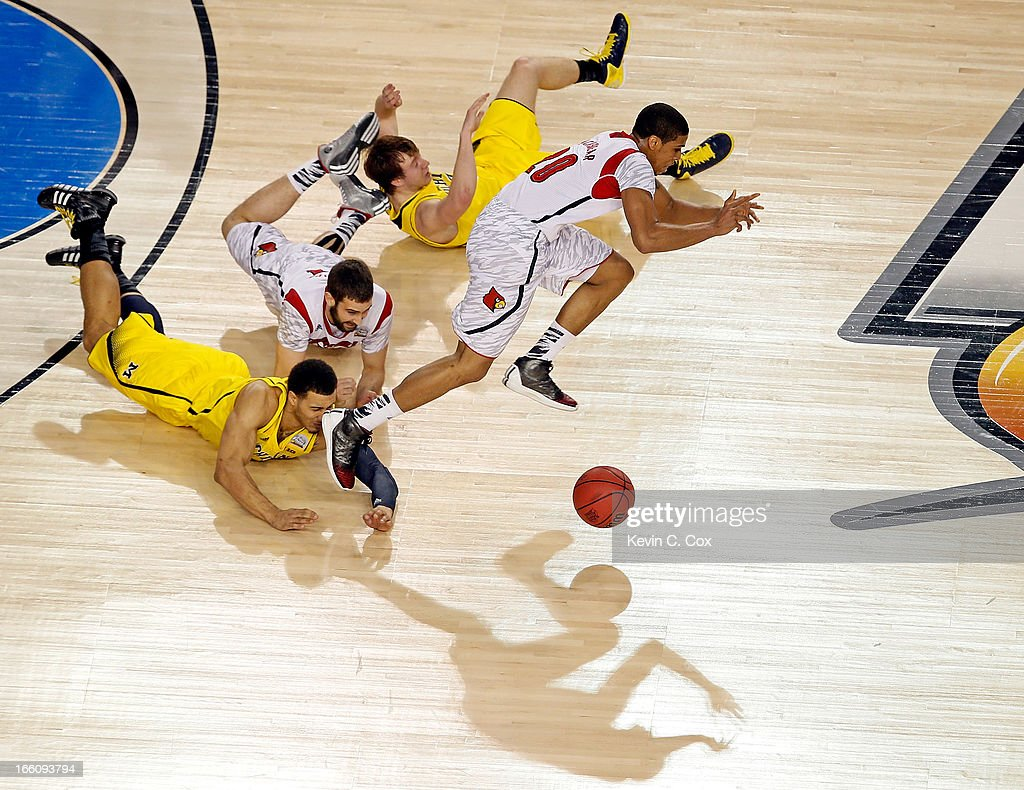 Wayne Blackshear of the Louisville Cardinals and Jordan Morgan of the Michigan Wolverines go after a loose ball in the first half during the 2013...