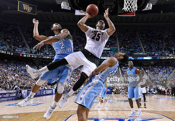 Wayne Blackshear of the Louisville Cardinals drives between Joel Berry II and Isaiah Hicks of the North Carolina Tar Heels during the quarterfinals...