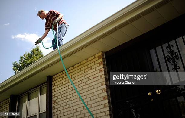 Wayne Bonnell is cleaning out roof gutter of Helen Hutchinson at Littleton Colo on Thursday June 7 2012 A new nonprofit called Village to Village...