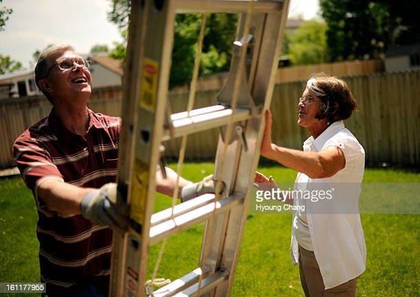 Wayne Bonnell left sets the Ladder by Helen Hutchinson before him start cleaning out house gutter of Hutchinson at Littleton Colo on Thursday June 7...